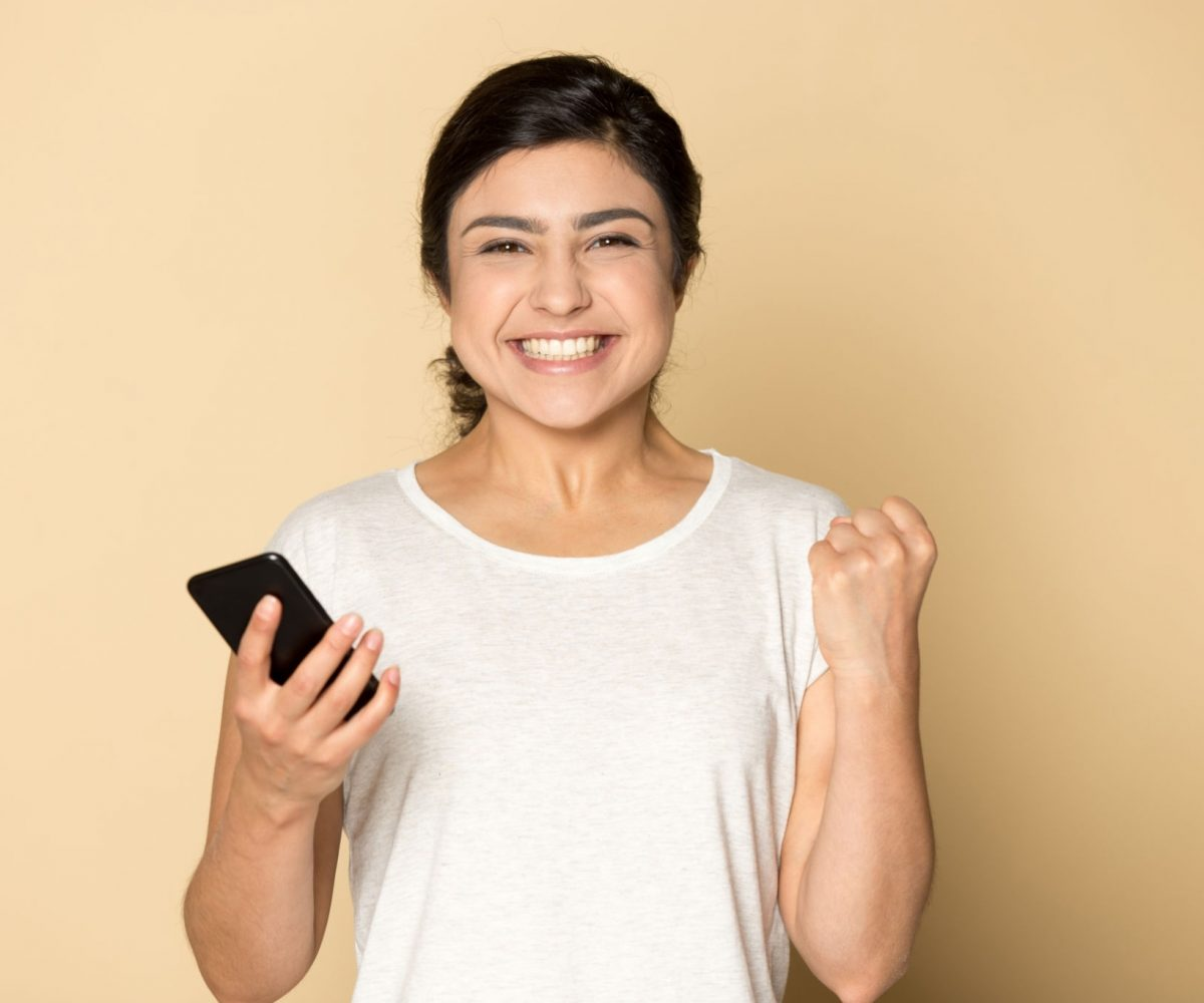 Happy young indian woman isolated on orange brown studio background look at camera excited with good cellphone message, overjoyed millennial ethnic girl pleased with amazing news on cellular phone